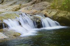Waterfall in the rocks in the forest stock image