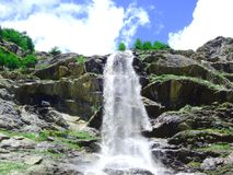 Waterfall. In rocks on a sunny day Royalty Free Stock Image