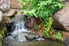 Waterfall in rocky garden Stock Images