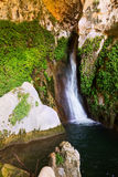 Waterfall in rocky grot Stock Photos