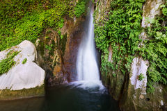 Waterfall in rocky grot Stock Images