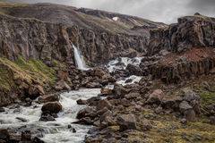 Waterfall in rocky Iceland. Waterfall in the rocky wild landscape of Iceland. Rocks are covered in green moss Stock Photos