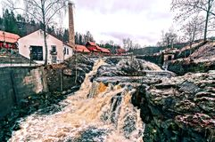 Waterfall rushing rivers. Colorful water containing iron compounds. Foundry, nestled in a narrow valley along the river Lomma.  HDR view. Norwegian winter Royalty Free Stock Photo