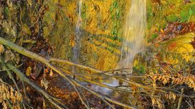Waterfall with it`s splashing water on the rock the woods. Two waterfalls with it`s splashing water on the ground seen through tree branches stock footage