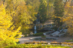 Waterfall scene in autumn park. Waterfall amidst rocks in autumn park covered with golden leaves Stock Photography