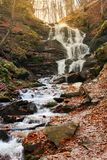 Waterfall Shypot of Carpathian mountains in autumn. Powerful stream of water. brown foliage on the rocks royalty free stock image