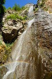 Waterfall with small rainbow. Royalty Free Stock Image