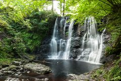 Waterfall with small water pond below surrounded by trees and lu stock photos