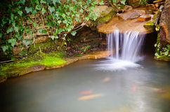 Waterfall spilling into pond Stock Photo