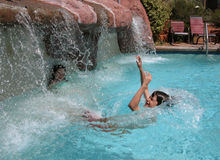 Waterfall Splash. A young girl and boy (brother and sister) playing in a waterfall in a swimming pool Stock Photography