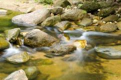 Waterfall with stone of green moss in rain forest , Kiriwong Village, kamloan, Lansaka, Nakhon Si Thammarat, Thailand. stock photo