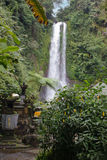 Waterfall with stone shrines and greenery in Bali countryside, Indonesia Stock Image
