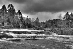 Waterfall with Stormy Clouds. Black and white waterfall surrounded by stormy clouds Royalty Free Stock Photography