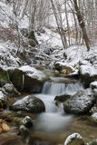 Waterfall of a stream. Soft waterfall of a mountain stream with ice and snow Stock Photos