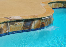Waterfall at the Suburban pool. A waterfall is shown on the edge of a suburban pool Stock Image