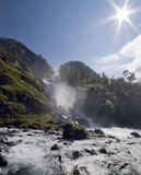 Waterfall and sun. The sun shining over a waterfall. Norway, Hordaland county landscape. oddadalen Stock Images