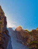 Waterfall with sunlight in the mountains, Ala-Archa, Kyrgyzstan. Stock Photo