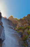 Waterfall with sunlight in the mountains, Ala-Archa, Kyrgyzstan. Royalty Free Stock Image
