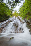 Waterfall surrounded by trees with green leaves Royalty Free Stock Photo