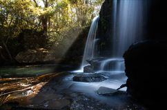 Waterfall and swimming hole in Southern Highlands. Sunlight streaming through trees of the surrounding bushland of a beautiful waterfall and swimming hole in royalty free stock image