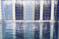 Waterfall on swimming pool. For use as relaxing and therapy concept royalty free stock photos