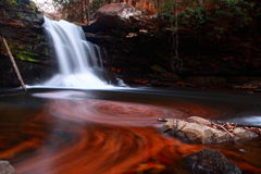 Waterfall and swirled patterns. Waterfall time exposure with fall colors and swirled patterns in the water Royalty Free Stock Photography