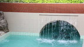Waterfall in thermal pool. Waterfall over the cave - indoor pool with thermal water and tropical plants stock footage