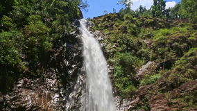 Waterfall from top among green rocks along foamy stream to pond stock video footage