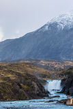 Waterfall in Torres del Paine National Park. Cloudy day over a nice Waterfall with a snow mountain in the background - Torres del Paine National Park Chile Stock Photography
