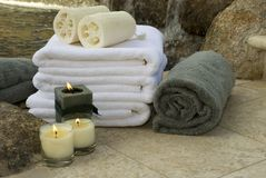 Waterfall towels 4. Towels and candles at waterfall spa with loofah sponge Royalty Free Stock Image