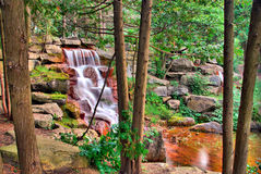 Waterfall Through The Trees. A waterfall cascades over red rocks into a calm pool. A second smaller waterfall is just visible on the right Stock Photos
