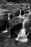 Waterfall trickling over rocks in black and white royalty free stock photos