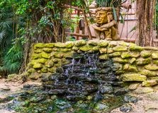 Waterfall in a tropical garden, streaming water over some rocks, stone sculpture decoration. A Waterfall in a tropical garden, streaming water over some rocks royalty free stock image