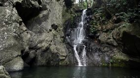 Waterfall in tropical jungle dark rock stock footage