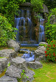 Waterfall in tropical zen garden. Natural waterfall surrounded by spring foliage in a zen garden Royalty Free Stock Photos