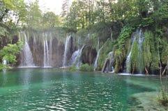 Waterfall into Turquoise Green Lake Stock Photos