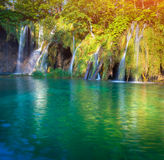 Waterfall with turquoise water and sunny beams Royalty Free Stock Photo