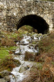 Waterfall under bridge. Scenic view of waterfall on hillside under ancient roman stone bridge Royalty Free Stock Photography