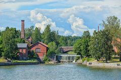 Waterfall in Vanhankaupunginkoski and old power station, Helsink Royalty Free Stock Photography