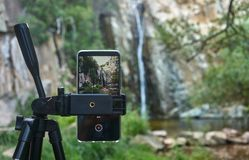 Waterfall view from a smartphone. Close up view of a smartphone filming a waterfall Royalty Free Stock Images