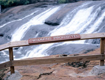 Waterfall warning sign. Swimming prohibited sign on fence overlooking waterfall Royalty Free Stock Image