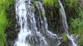 Waterfall water splashing from rocks, green fresh grass, beautiful spring cascade. UHD 4K stock footage