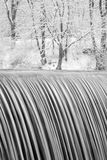 Waterfall in Winter. Waterfall flowing over dam surrounded by trees in winter. Vertically framed shot Stock Image