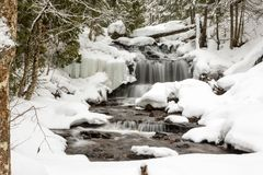 Waterfall in Winter Wonderland. Waterfall in Winter. Wagner Falls in Munising Michigan, surrounded by freshly fallen snow. Snow lines tree branches and lacy ice Stock Photo