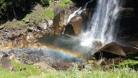 Waterfall yosemite. Waterfall in Yosemite national park with nice rainbow and fresh green gras Royalty Free Stock Images