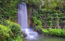 Waterfall in zen garden. Natural waterfall surrounded by green spring foliage in a zen garden Stock Photos