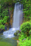 Waterfall in zen garden. Natural waterfall surrounded by greenspring foliage in a zen garden Royalty Free Stock Photo