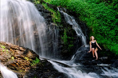 Waterfalls  beauty. Woman lounges by the falls Royalty Free Stock Photos