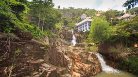 Waterfalls Cascade on Mountain River Green Slopes Houses. Panorama of waterfalls cascade on mountain river among green slopes and resort houses at background stock video footage