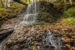 Waterfall over lush greens and golden fall foliage. Waterfalls flow smoothly over rocks surrounded by peak fall foliage in Delaware Water Gap section of Pocono Stock Photo